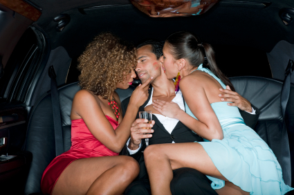 Two young women enjoying the company of a young man in the back of a limo.